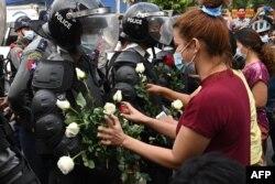 Протестующие вставляют цветы в щиты полицейских во время протестов в Янгоне, 6 февраля.