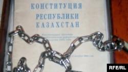 """""""Азат"""" партиясынын активисттери Нурсултан Назарбаевди өмүр боюу президент кылуу демилгесин көтөргөн актөбөлүк профессор Закратдин Байдосовго Конституциясын чынжырга оролгон үлгүсүн жөнөтүшкөн. Талдыкоргон, 2009-жыл, сентябрь."""