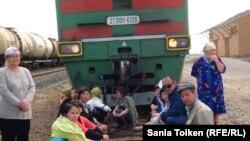 Участники акции протеста сидят на рельсах, преградив путь пассажирскому поезду. Поселок Доссор, 5 мая 2011 года.