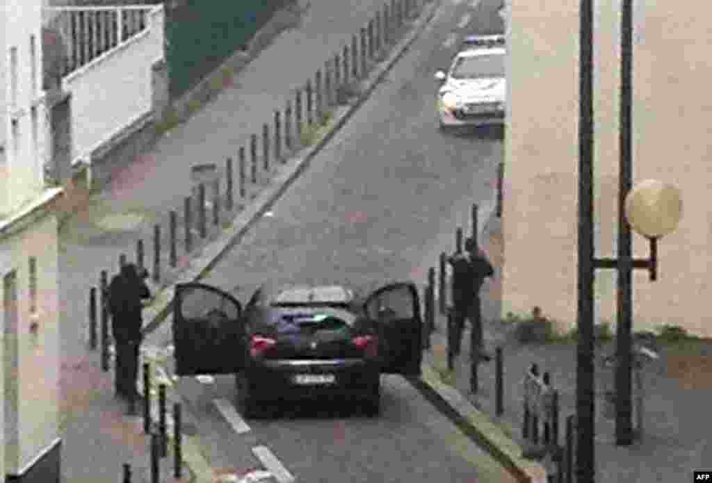 Armed gunmen face police officers near the offices of Charlie Hebdo.