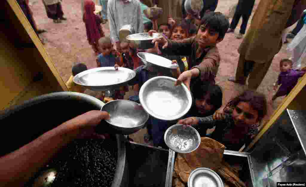 Children hold their bowls as they wait in line for a charity food handout in Peshawar, Pakistan. (Reuters/ Fayaz Aziz)