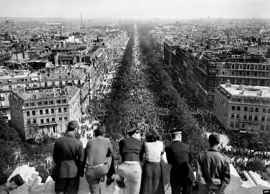 Люди спостерігають за юрбою, яка збирається біля Тріумфальної арки в Парижі, 8 травня 1945 року
