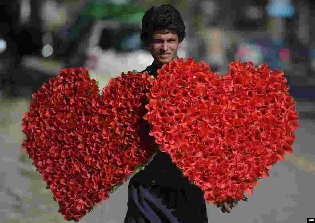 A Pakistani vendor carries heart-shaped bouquets for sale ahead of Valentine's Day along a street in Islamabad on February 12