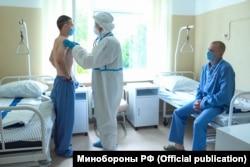 Измерение температуры добровольца во время врачебного осмотра в Сеченовском университете, где Министерство обороны РФ совместно с Национальным исследовательским центром имени Гамалеи проводит эксперимент по испытанию вакцины от коронавируса