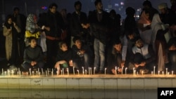 Pakistani civil society activists place lit candles during a vigil in Lahore on December 18 for the children and teachers killed in an attack by militants on an army-run school in Peshawar.