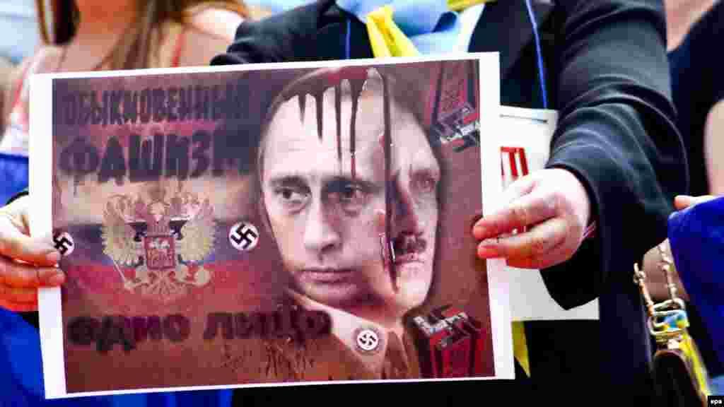 Плакат учасниці протесту проти агресії Росії напередодні візиту до Італії російського президента Володимира Путіна. Мілан, 9 червня 2015 року