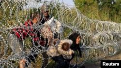 Мигранты из Сирии пытаются пролезть через ограждение на территорию Венгрии. 27 августа 2015 года.