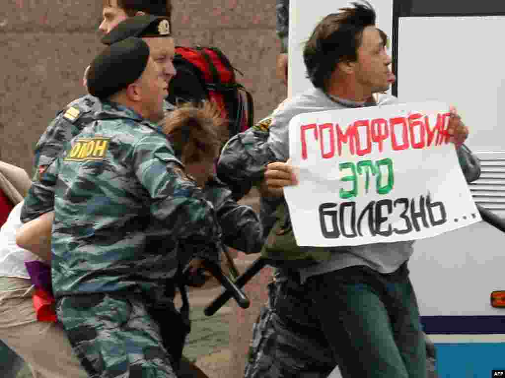 "Police arrest a gay-rights activist as he holds a poster reading ""Homophobia Is A Disease"" during an unsanctioned gay-pride rally in St. Petersburg on June 25, 2011."