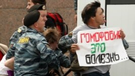 "Russian police arrest a gay-rights activist holding a poster reading ""Homophobia is a disease"" during a banned gay-pride rally in St. Petersburg in June."
