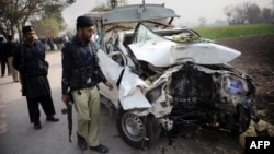 Pakistani police examine the wreckage of a bomb-disposal vehicle after a roadside bomb explosion on the outskirts of Peshawar on December 16.