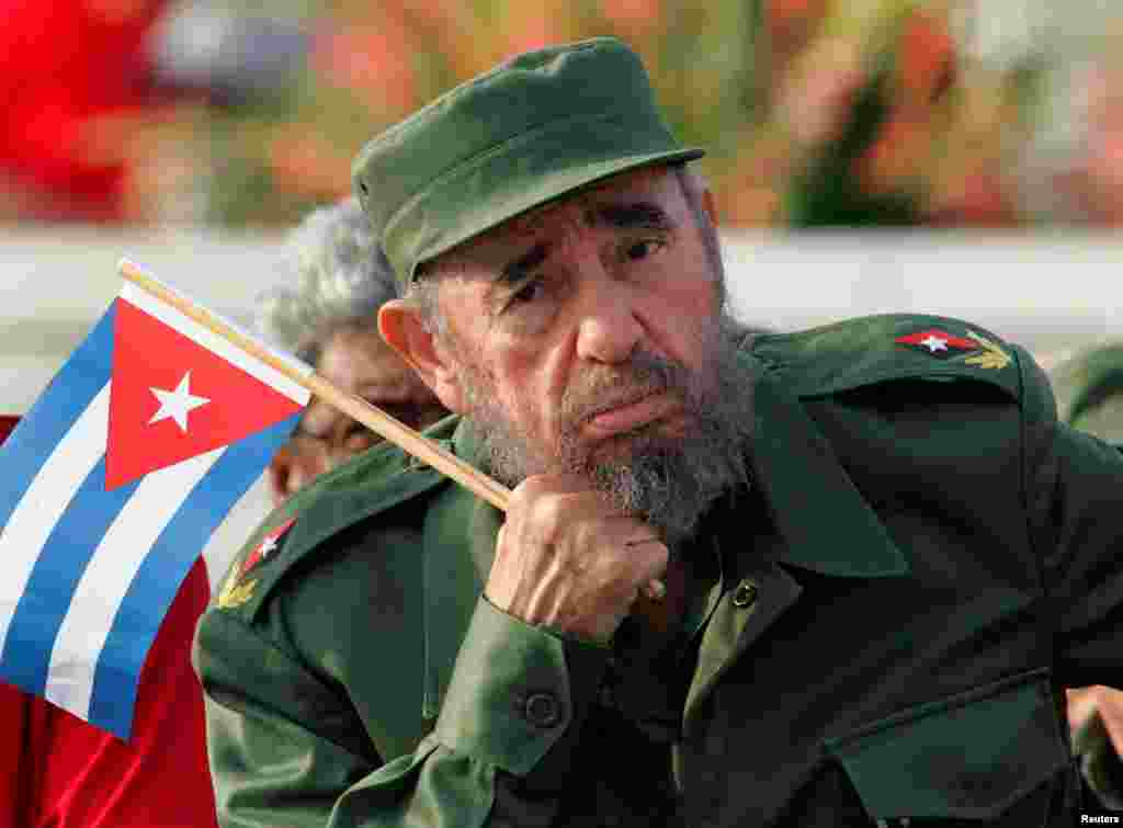 Holding a Cuban flag, Castro listens to a speaker during the May Day parade in Havana's Revolution Square in 2005.