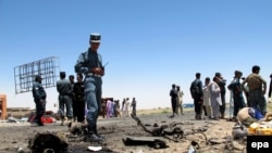 Afghan security officials inspect the site of a suicide bomb blast that targeted the national security forces convoy in Helmand province on July 21, 2014.