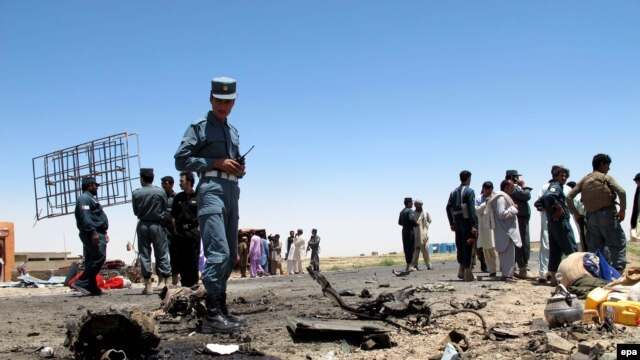 Afghan security officials inspect the site of a suicide bomb blast that targeted a security convoy in Lashkar Gah, in Helmand Province, on July 21.