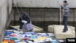 Громадянські активісти виловлюють документи з річки у Межигір'ї. 21 лютого 2014 року