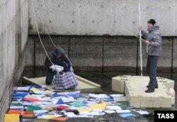 """Активисты вылавливают бумаги и документы из водоема в президентской резиденции """"Межигорье"""" близ Киева. 21 февраля 2014 года."""