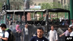 Cairo : Egyptians walk past a burnt armed forces bus at Tahrir Square in Cairo on April 9, 2011
