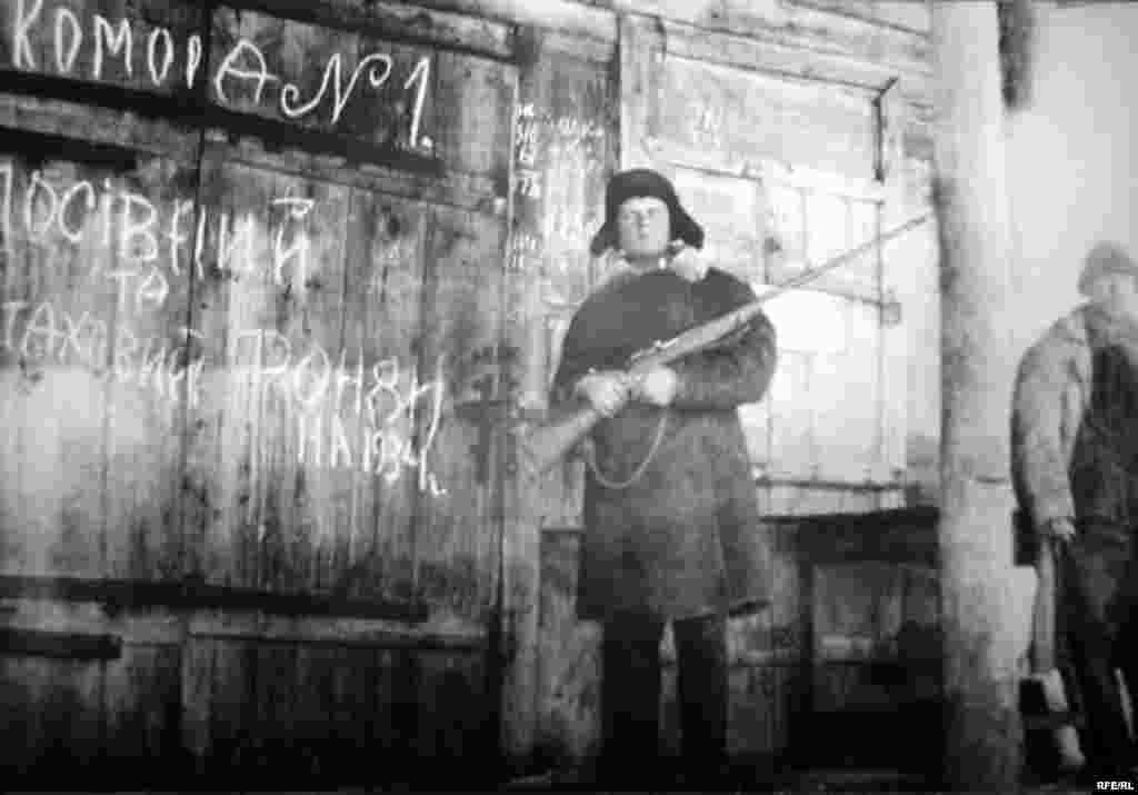 Член сільгоспартілі ім. Г. Петровського на Харківщині охороняє насінневий і страховий фонди господарства, 1933 р. - Голодомор, голод, 1933