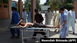 Afghan volunteers carry an injured youth on a stretcher to a hospital following an attack that targeted an education department compound in Jalalabad on July 11.