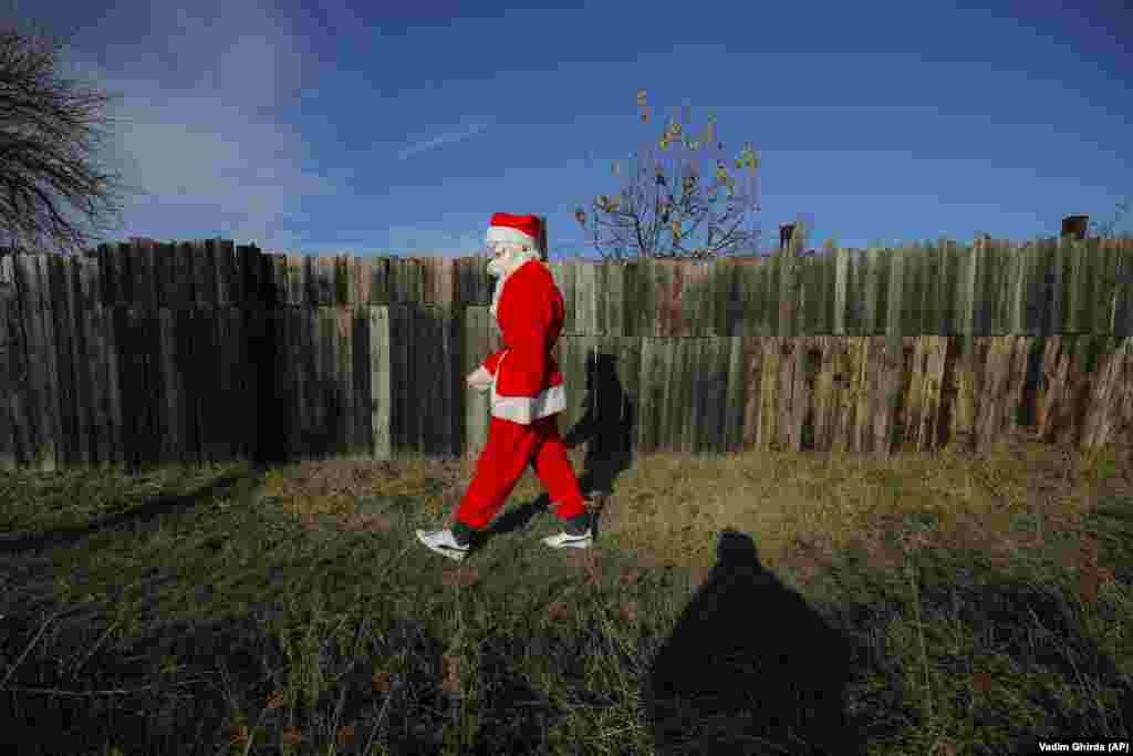 A Romanian charity worker wearing a Santa Claus costume departs after delivering Christmas presents to a poor family on the outskirts of Brasov. (AP/Vadim Ghirda)