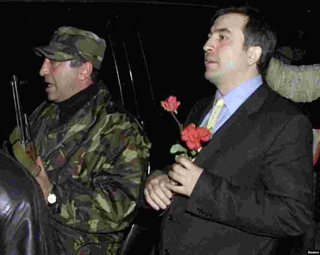 "Georgian opposition leader Mikheil Saakashvili (right), surrounded by his bodyguards, leaves after a meeting with President Shevardnadze in the presidential residence in Tbilisi on November 23. Shevardnadze announced his resignation, bowing to opposition protesters who stormed parliament and declared a ""Rose Revolution"" in the former Soviet republic."