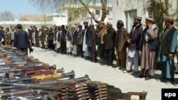 Fighters from the Hizb-e Islami militia surrender their arms to Afghan police in Baghglan Province on March 8.
