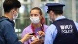 Belarusian athlete Krystsina Tsimanouskaya talks with a police officer at Haneda airport in Tokyo on August 1.