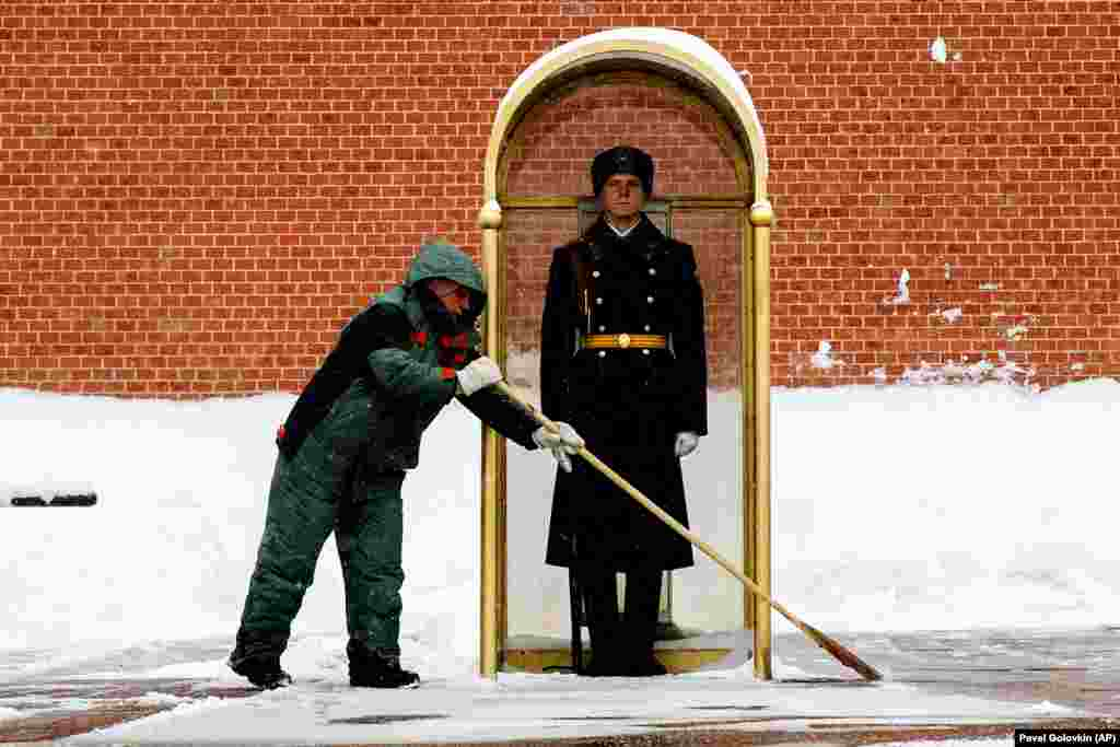 A municipal worker clears snow as an honor guard soldier stands in his station at the Tomb of Unknown Soldier in Moscow. The weekly temperature in Moscow is around minus 12 degrees Celsius during the day and drops to minus 18 degrees at night. (AP/Pavel Golovkin)