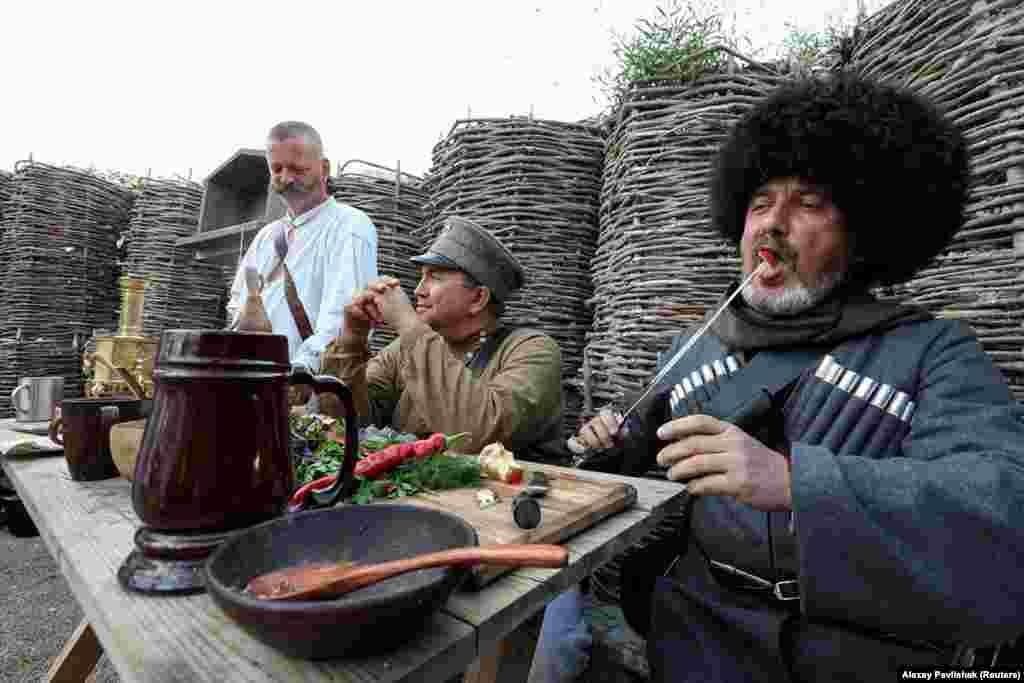 Мужчины во время обеда в день реконструкции битвы. На сайте «парка» говорится, что в новом тематическом пространстве «оживет двухтысячелетняя история Крыма» и это место станет «мощным культурно-образовательным центром, привлекающим крымчан и туристов со всей России».