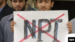 A demonstrator outside the Iranian presidential palace in 2003 holds a sign registering disapproval for the Nuclear Nonproliferation Treaty, of which Iran is a signatory.
