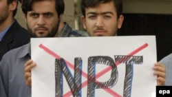 "Iranians expressing anti-NPT sentiment at an Islamist-staged protest outside Tehran's presidential palace in October 2003, after Iranian officials indicated they would sign the NPT's ""additional protocols."""