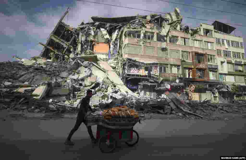 A Palestinian man walks past a destroyed building in Gaza City on May 20, 2021 after it was bombed by an Israeli air strike.