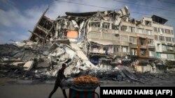 یو ډوډۍ خرڅوونکی په غزه کې د اسراییلو په بمبارۍ کې د ړنګې ودانۍ مخې ته تېرېږي - د ۲۰۲۱ز کال د مې ۲۰مې انځور