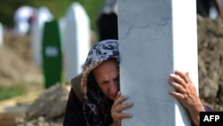 Bosniýaly zenan Srebrenisa gyrgynçylygynda heläk bolan we jesetleri täze tapylan 775 adamyň jaýlanyş çäresinde mazar daşyny gujaklaýar, Bosniýa-Gersogowina, 11-nji iýul, 2010-njy ýyl.