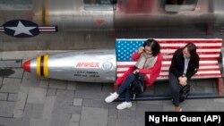 Китайские женщины сидят на скамейке с флагом США у магазина одежды в Пекине