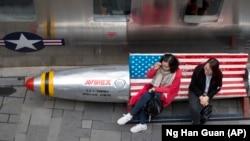 Жительницы Китая на скамейке, выкрашенной под американский флаг, у входа в магазин одежды с товарами из США. Пекин, 23 марта 2018 года.