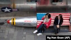 Китайские женщины сидят на скамейке с флагом США у магазина одежды в Пекине.