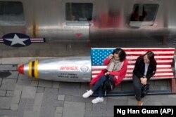 Китаянки у магазина американской одежды в Пекине.