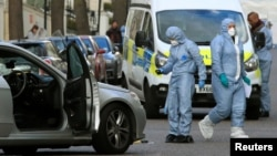 Police forensics officers work at the site where a vehicle rammed the parked car of Ukraine's ambassador outside the Ukrainian Embassy in London on April 13.