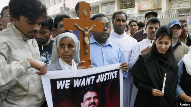 Pakistanis hold a cross and a poster of slain Minister for Minorities Shahbaz Bhatti during a protest in Hyderabad after his killing.