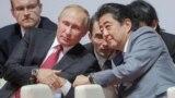 Russian President Vladimir Putin (left) and Japanese Prime Minister Shinzo Abe (right) talk on the sidelines of the Eastern Economic Forum in Vladivostok in September.