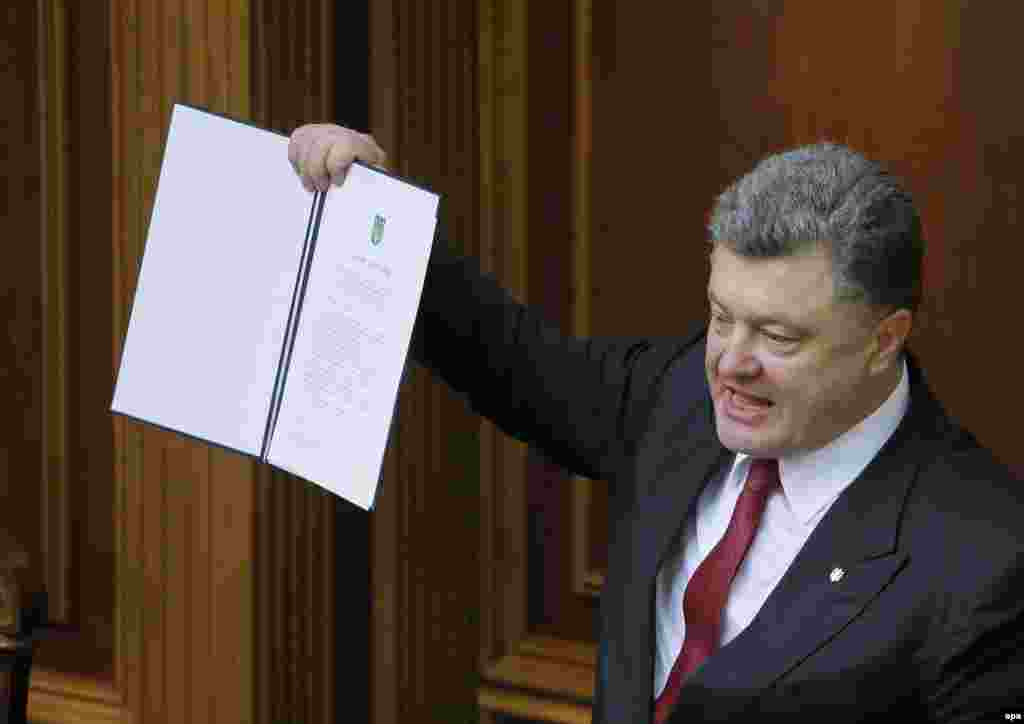 Ukrainian President Petro Poroshenko shows a signed landmark Association Agreement with the European Union during a session of the parliament in Kyiv on September 16. (epa/Sergei Dolzhenko)