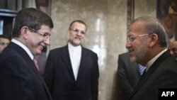 Turkish Foreign Minister Ahmet Davutoglu (left) at a chance meeting in Lisbon with his Iranian counterpart, Manuchehr Mottaki, in mid-July