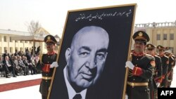 Army officers carry a portrait of former President Mohammad Daud Khan during his funeral in Kabul.