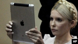 Yulia Tymoshenko uses her iPad to take a photograph during a trial hearing in Kyiv last month.