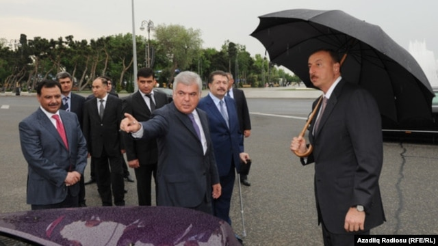Azerbaijani Transport Minister Ziya Mammadov (center) and Baghlan Group owner Hafiz Mammadov (behind him) present London taxis to President Ilham Aliyev (right).