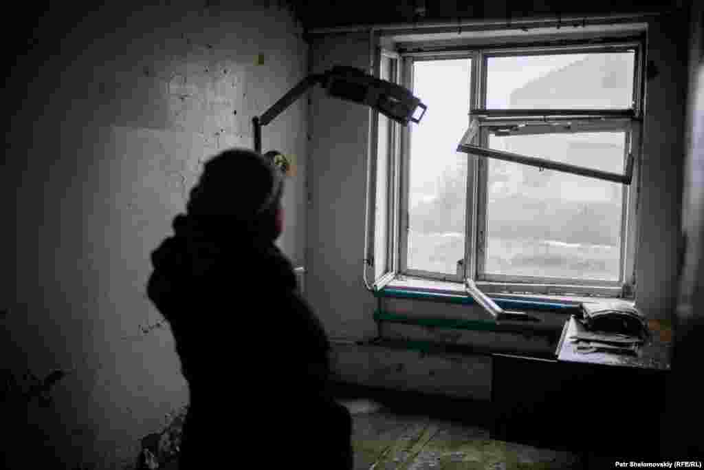 Marchenko stands inside a health clinic damaged by fighting.