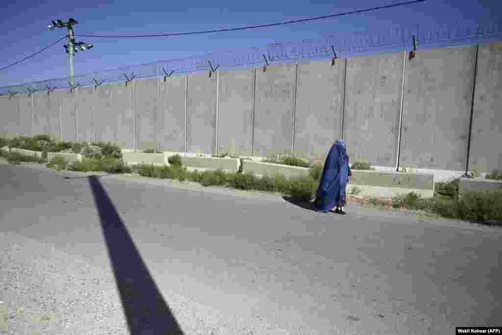 Жанчына праходзіць каля былой вайсковай базы ЗША ў Баграме 1 ліпеня. Некаторыя мусульмане-фундамэнталісты інтэрпрэтуюць дыскусійныя ўрыўкі з Карану як патрабаваньне да жанчын быць цалкам закрытымі, калі яны знаходзяцца ў публічным месцы.