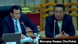 Bo'yinbog' taqqan vitse-spiker (chapda) bo'yinbog'siz hukumat amaldoriga tanbeh bermoqda.