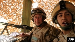 Britain's Prince Charles listens to a British soldier at Camp Pimon in Helmand Province.