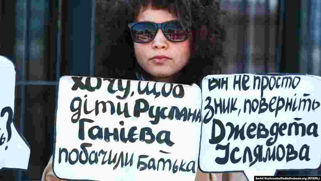 Bu qız qolunda Qırımda ğayıp olğanlardan Ruslan Ganiyev ve Cevdet İslâmovnıñ adları ile levhalarnı tuta
